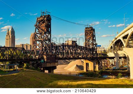 An old railroad lift bridge and a new freeway bridge span the Cuyahoga river in Cleveland Ohio with the downtown skyline in the background
