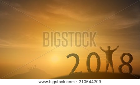 2018 Silhouette man stand on the top of mountain and look through the sunrise sunset and give two hand up to feel like a winner success finishreach a goal of live jobswork in 2018 new years