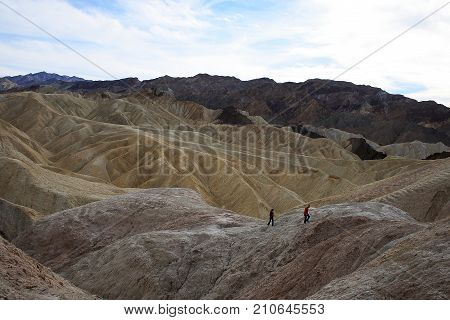 DEATH VALLEY, CALIFORNIA - NOVEMBER 28 2009: Two people at Zabriskie Point in Death Valley National Park California