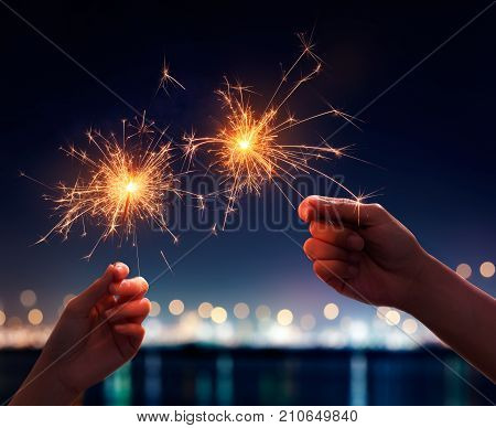 Couple hand holding a burning light sparklers