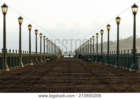 Pier with solitary person lined with streetlamps, San Francisco Bay
