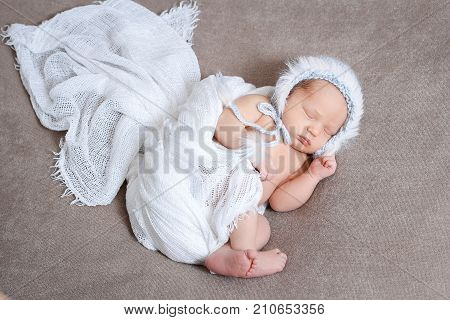 Sleeping newborn baby girl in a gently blue knit hat. Sleeping on a covered sheet.