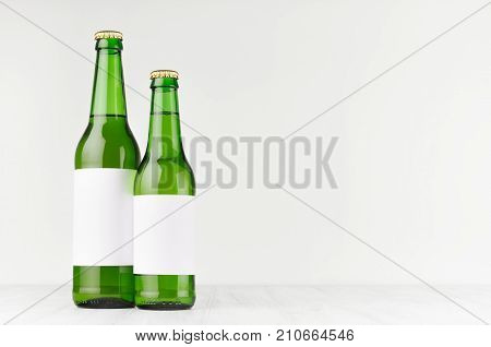 Green beer bottles longneck 500ml and 330ml with blank white label on white wooden board mock up. Template for advertising design branding identity.