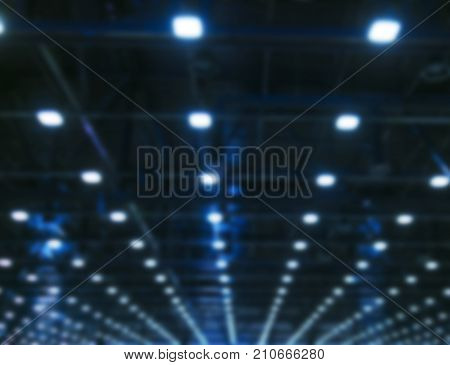 Blurred background Lights and ventilation system in long line on ceiling of the dark office industrial building Blur exhibition Hall Ceiling construction