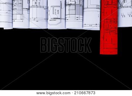 Architectural blueprints and blueprint rolls and a drawing instruments on the black worktable background. Drawing compass plans.Construction background.with red rolled blueprint