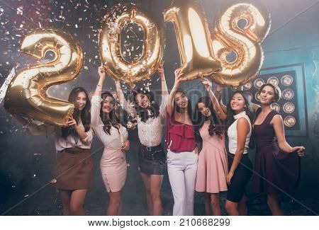 Happy 2018 Year! Hand's up! Fun is all we need!  Beautiful group of smiling girls carrying gold colored numbers 2018 overhead and throwing confetti