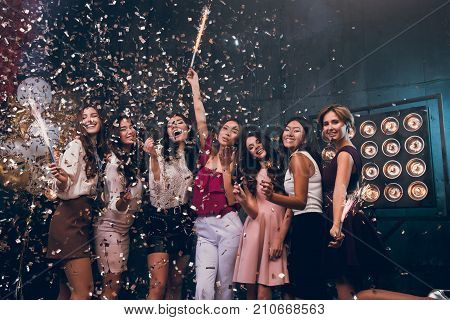 Fun is all we need! Group of beautiful young people dancing together and looking happy. Company of a beautiful dress dancing and smiling with a sparkle and gold confetti. Happy Hew 2018 year! Warmest Wishes For Christmas!