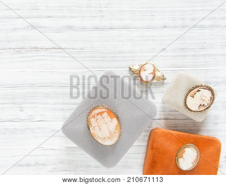 Woman's Jewelry. Vintage jewelry background. Beautiful vintage cameo brooches and jewelry boxes on white background. Flat lay, top view