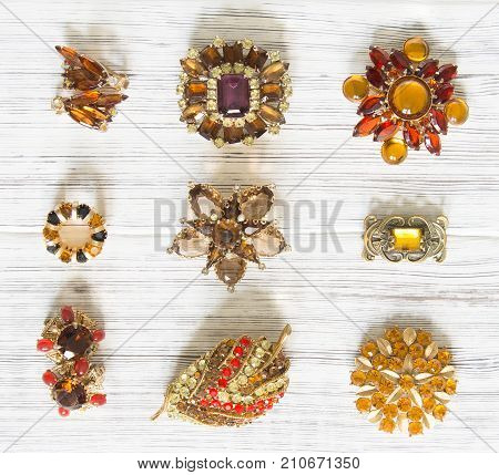 Woman's Jewelry. Vintage jewelry background. Beautiful bright rhinestone brooch and earrings on white wood. Flat lay, top view.