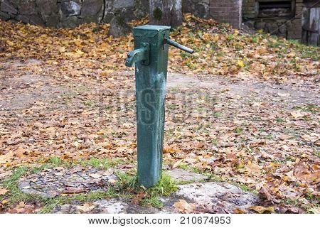old green antic water pomp autumn background in Kuldiga Latvia