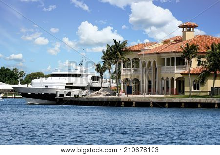 A mansion on the canal with a yacht tied up alongside