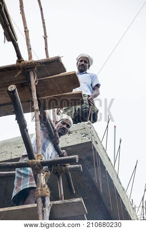 PONDICHERY PUDUCHERY INDIA - SEPTEMBER 04 2017. An unidentified man works at heights on a very insecure scaffolding. Concept of WORKING AT HEIGHTS