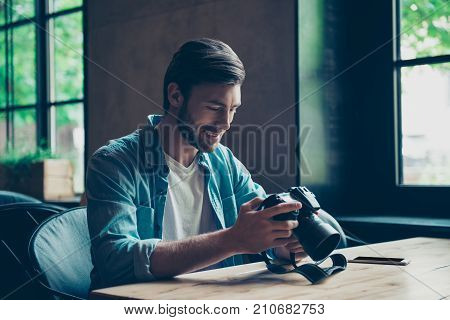 Cheerful Dreamy Brunet Hipster Traveller Is Watching His Shoots At Cafe With Camera. He Is A Graphic