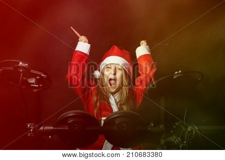 Little caucasian girl drummer disguised as Santa Claus playng the electronic drum kit, emotional portrait on black background. Copy space.