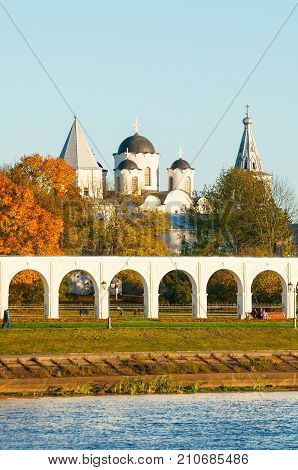 Architecture landscape of Veliky Novgorod Russia. Arcade of Yaroslav Courtyard and ancient St Nicholas cathedral with towers at autumn sunset in Veliky Novgorod Russia poster