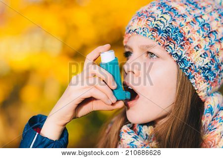 Asthma Patient Girl Inhaling Medication For Treating Shortness Of Breath And Wheezing In A Park