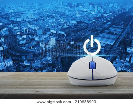 Power button with wireless computer mouse on wooden table over city tower street and expressway Start up business concept
