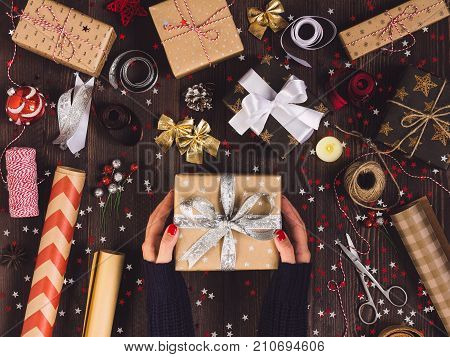 Process of package christmas gift box. Woman in hand holding new year gift box. Christmas packaging wrapping paper ribbon twine bow and thread scissors christmas balls on wooden background