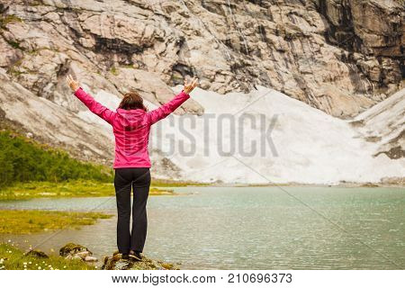 Travel concept. Happy free tourist woman in happiness and elated enjoyment with arms raised outstretched up looking at mountains in Norway