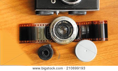A still life of accessories from old film camera: camera, lens, film cassette, piece of film, film container.