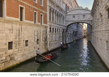 Venice, Italy - September 21 2017. Gondoliers ferry tourists around passing under landmark the Bridge of Sighs (Ponte dei Sospiri) in Venice Italy.