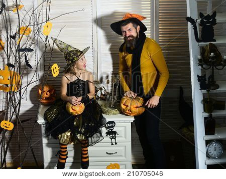 Wizard And Little Witch In Hats Carve Pumpkins.