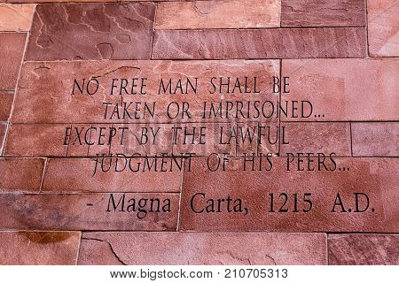 Article of Magna Carta text on of the old brick wall
