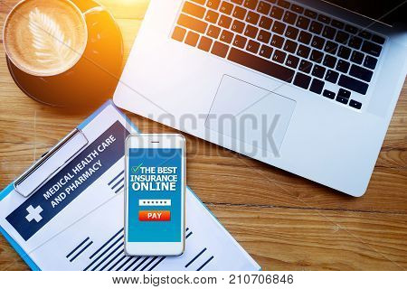 medical health care insurance online concept : medical health care policy document on clipboard with laptop and insurance online screen on mobile phone. Website application for apply insurance online