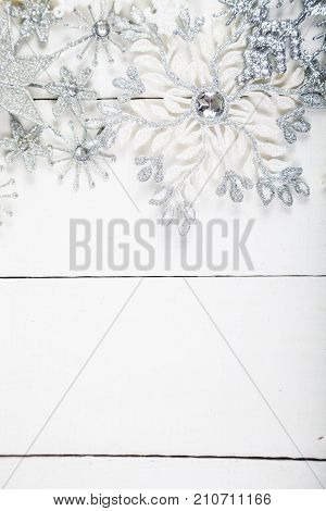 Silvery Snowflakes On A White Wooden Background.