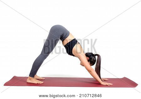 young asian woman doing yoga in Adho Mukha Svanasana or Downward-Facing Dog yoga pose on the mat isolated on white background exercise fitness sport training healthy lifestyle and people concept