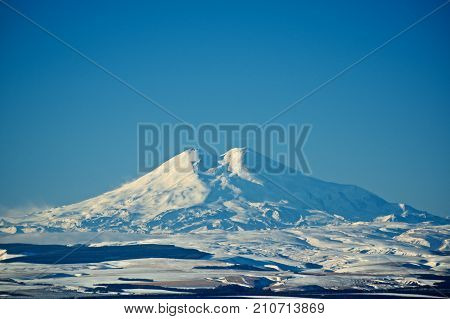 Two Beautiful Snowy Mountain Peaks of Caucasus Range against Blue Sky in Sunny Winter Day Outdoors