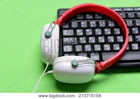 Headphones And Black Keyboard. Earphones In Red And White Colors