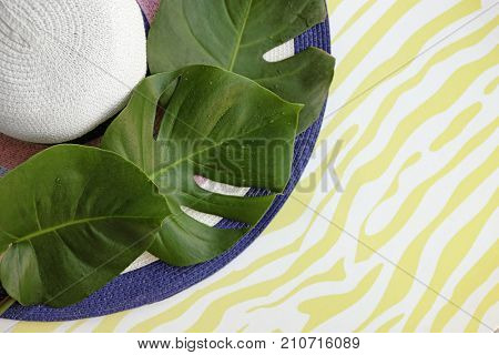 Hat with monstera leaves on color background