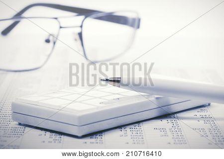 Financial accounting. Pen and calculator on balance sheets