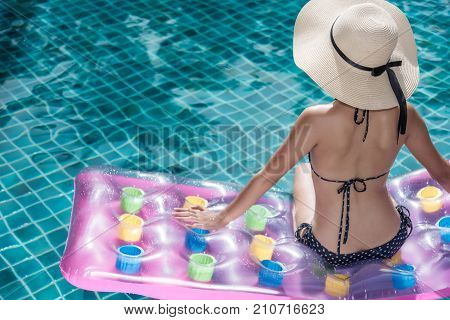 Portrait of beautifu woman relaxing in bikini and big hat sit on air mattress in swimming pool blue water