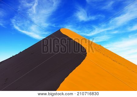 The most ancient in the world Namib Desert. Sharp border of light and shade on a dune crest at sunset. Namibia, South Africa