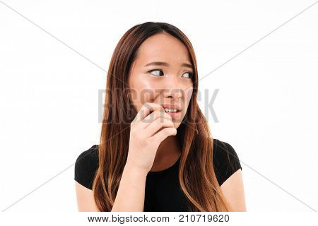 Close-up portrait of scared young asian woman standing with finger in her mouth, lookin aside, isolated over white background