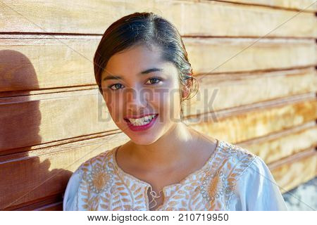 Mexican latin woman with ethnic dress smiling in wooden background