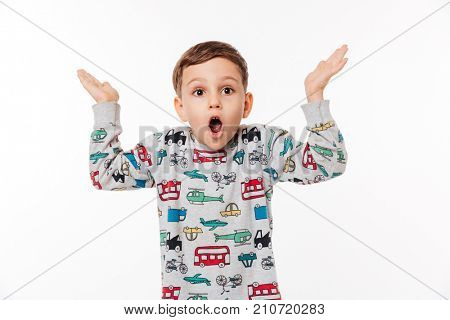 Portrait of a surprised little kid standing and shrugging shoulders isolated over white background