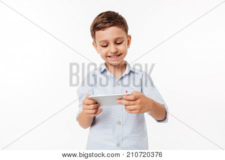 Portrait of a satisfied cute little kid playing games on smartphone isolated over white background