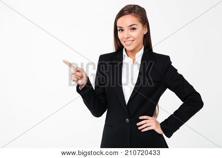 Image of happy business woman standing isolated over white background. Looking camera pointing to copyspace.