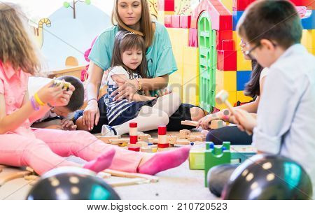 Dedicated young female kindergarten teacher holding a pre-school shy girl while watching children during playtime with wooden toy blocks in the classroom