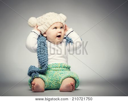 Small cute boy sitting on the ground, dressed in wool beanie, a scarf and pants, looking happy.