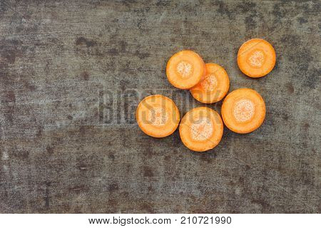 Slices of fresh winter carrot on a grungy metal background