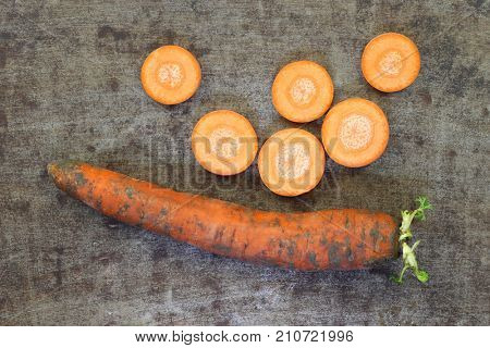 Winter carrot and some slices on a grungy metal background