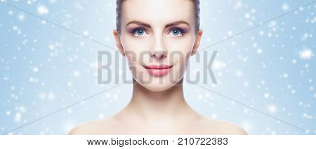 Portrait of young, beautiful and healthy woman: over winter background. Healthcare, spa, makeup and face lifting concept.