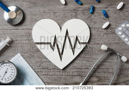Top view of doctor desk with heart shape showing cardiac signs, medicine and stethoscope. High angle view of white shaped heart icon with electrocardiogram. Cardiology and healthcare concept.
