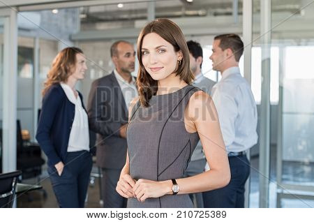 Successful formal woman standing in front of businesspeople and smiling. Portrait of confident and proud businesswoman with team at modern office. Beautiful satisfied businesswoman looking at camera. poster