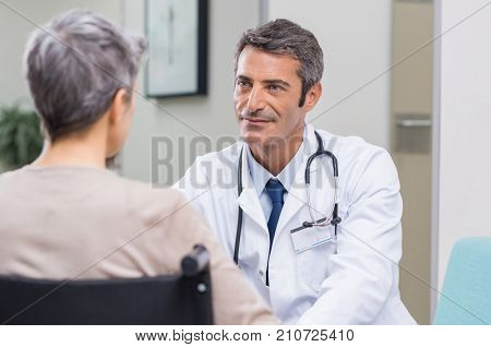 Doctor talking to woman in wheelchair after surgery. Portrait of a mature doctor talking to a senior disabled patient on wheelchair. Confident mature general practitioner in conversation at hospital.