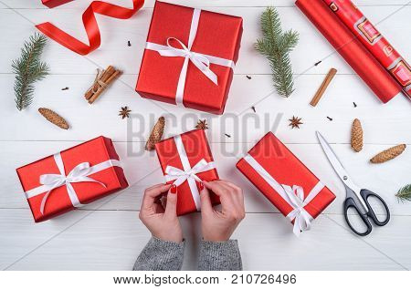 Christmas gift wrapping background. Female hands packaging christmas present with white satin ribbon top view. Winter holidays concept flat lay. Woman holding red Christmas gift
